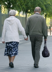 An elderly couple is holding hands while