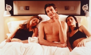 Two young women and a man in bed. --- Image by © M. Deutsch/Corbis